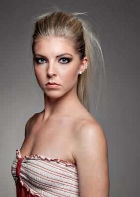 Dramatic headshot of female fashion model with bare shoulders and striking eyes