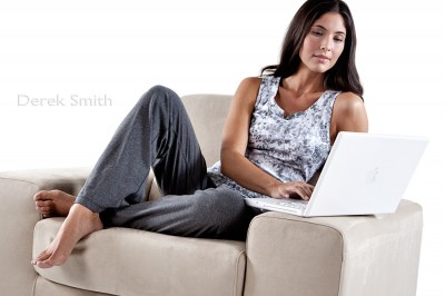 advertising photograph of attractive young caucasian woman with dark hair using laptap computer at home