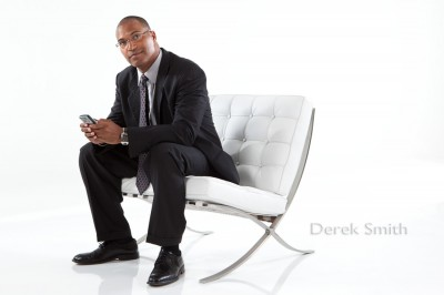 advertising photograph of handsome African American business man texting with smart phone while sitting on stylish white leather chair