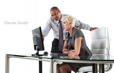 Two office workers viewing computer with stylish business desk and chair