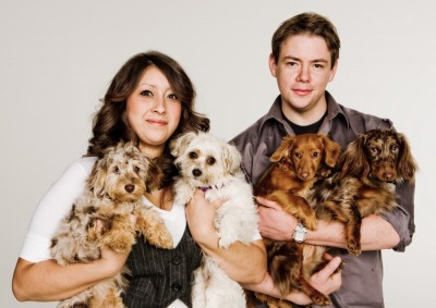 Studio portrait of handsome couple holding four small dogs