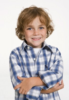 photograph of cute boy with big blue eyes and curley hari shot in the studio against a white background