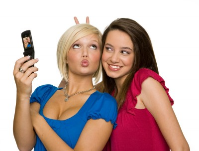 cute girls with cell phone pulling faces for selfie photographed in the studio for communications client