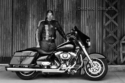 Black and white portrait of a man standing with his Harley Davidson motorcycle from Derek Smith's portfolio