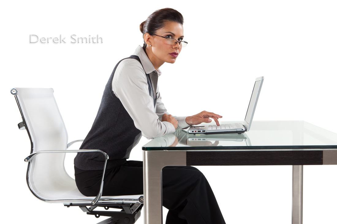 of an attractive business woman at stylish desk using laptop computer