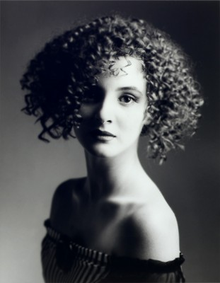 black and white studio photograph of attractive young model with curly hair