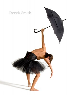 photograph of female modern dancer with black tutu and umbrella in white studio by Derek Smith