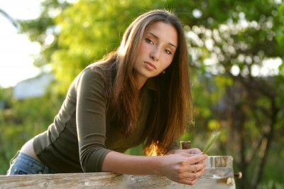 outdoor portrait of beautiful young woman with almond shaped eyes