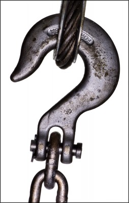 abstract photograph of heavy hook and chain against a white studio background