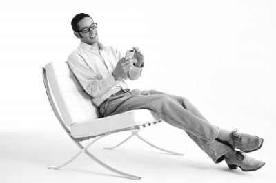advertising photograph of hip young professional man sitting in stylish leather chair using his smart phone