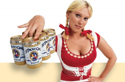 Attractive blonde girl in red lederhosen with six pack of beer for contraversial billboard campaign nice cans