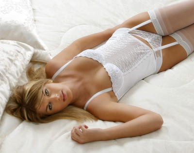 professional photograph of beautiful young woman wearing white lengerie and stockings on white bed