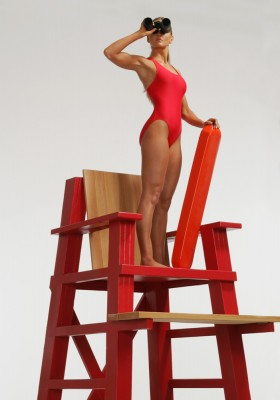 healthy and fit female life gaurd in red bathing suit on red tower with binoculars being watchful