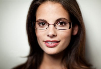 commercial headshot of dark haired beauty wearing fashion eyewear with soft focus and nice lips