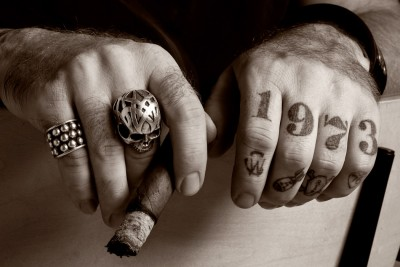 Dramatic black and white photograph of man's tattooed knuckles with large skull ring and cigar