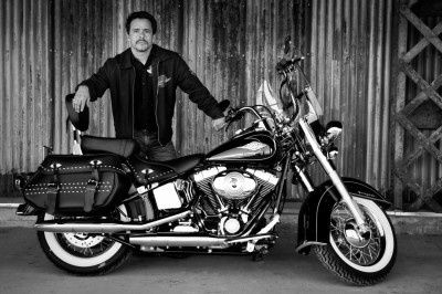 dramatic black and white portrait of a man with his Harley Davidson motorcycle