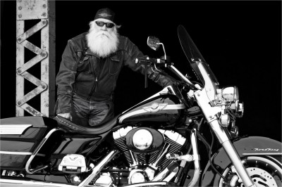 black and white photograph of man with long white beard and his Harley Davidson motorcycle by Derek Smith