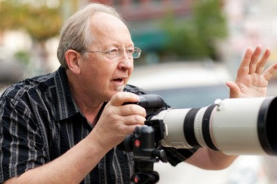 Photo of Derek Smith using camera with long lens on location