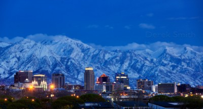 dramatic photograph of Salt Lake City skyline at dusk with snow covered mountains in the background